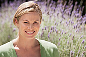 Caucasian woman smiling in lavender field, Cape Town, Western Cape, South Africa