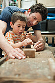 Caucasian father and son working in woodshop, Cape Town, Western Cape, South Africa