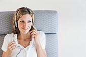 Woman listening to headphones in armchair, Palma de Mallorca, Balearic Islands, Spain