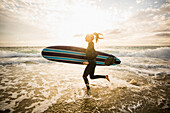 Caucasian surfer carrying board in waves, Los Angeles, California, USA