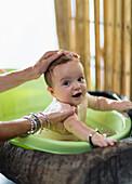 Caucasian mother bathing baby in plastic tub, Ubud, Bali, Indonesia