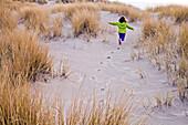 Caucasian girl running on sand dunes, Cannon Beach, Oregon, United States
