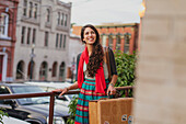 Mixed race woman carrying suitcase on city street, Charlottesville, VA, USA