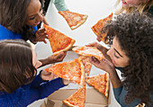 Women eating pizza together, Jersey CIty, New Jersey, USA