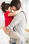 Hispanic mother and daughter hugging, Jersey City, New Jersey, USA