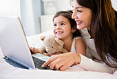Hispanic mother and daughter using laptop together, Jersey City, New Jersey, USA