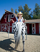 Mixed race girl laying on horse on ranch, San Rafael, California, USA
