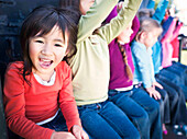 Group of little girls raising hands, close up on smiling girl