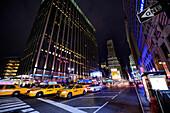 7e avenue night cirulation taxis, buildings, U.S. flags on the left