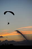 France, Montaigu, Vendée, paramotor flight at sunset. Water jet behind the veil