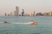 'Jet skiers with the skyline of Abu Dhabi in the background; Abu Dhabi, United Arab Emirates'