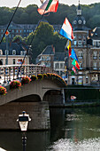 'Bridge with flags crossing the river; Dinant, Ardennes, Belgium'