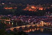 'View of the city of Heidelberg at nighttime and a bridge crossing the River Neckar; Heidelberg, Baden-Wurttemberg, Germany'