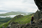 'A woman stands along on a rocky ridge looking out over the landscape of hills and water; Skye, Scotland'