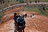 'Tourists walking up Uluru, formerly known as Ayers Rock; Northern Territory, Australia'