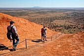 'Tourists walking up Uluru, formerly known as Ayers Rock; Northern Territory, Australia'