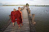 'Buddhist monks walk across U Bein Bridge, made of Teak wood; Mandaly, Burma'