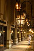 'Man in traditional arabic dishdasha outfit walking along corridor in shopping mall; Dubai, United Arab Emirates'