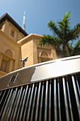 'Detail of chrome plated Rolls Royce beneath palm tree and traditional arabic style hotel with the Burj Khalifa behind; Dubai, United Arab Emirates'