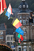 'International flags mounted in a row with buildings in the background; Dinant, Belgium'