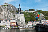 'A church and other buildings along the water and flags flying; Dinant, Belgium'