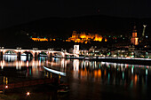 'Heidelberg Castle and the old bridge over River Neckar illuminated at nighttime; Heidelberg, Germany'