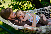 Father And Daughter Relaxing On Hammock