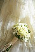 Flower Bouquet Against Wedding Dress