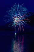 Fireworks Over The Water With A Mountain In The Background