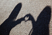 Shadow Of Two People Shaping A Heart With Their Hands