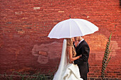 A Bride And Groom Under A White Umbrella