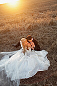 'A Bride And Groom Sitting In A Field; St. Catherine's, Ontario, Canada'