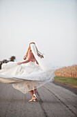A Bride Spinning In Her Dress On The Road