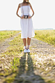 A Bride Standing On A Dirt Road In A Field With A Camera Around Her Neck