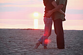 'A Couple Standing Together On A Beach At Sunset; St. Catherine's, Ontario, Canada'