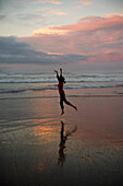 'A Girl Dances On The Beach At Sunset; Waihi Beach, New Zealand'