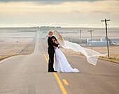 'Bride And Groom Posing On A Rural Road; Threehills, Alberta, Canada'