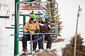 'A Man And Woman Riding A Chair Lift At A Ski Area; Red Deer, Alberta, Canada'