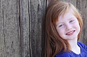 'A Young Girl Leaning Against A Barn; Gresham, Oregon, Usa'