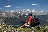 'Male Hiker Sitting On Top Of A Ridge Overlooking A Mountain Valley And Lake; Alberta, Canada'