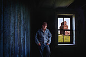'Portrait Of A Farmer/Rancher In An Old Abandoned Ghost Town Store With A Grain Elevator Seen Out The Window; Bents, Saskatchewan, Canada'