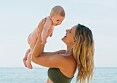 'A Mother Plays With Her Baby On The Beach; Banalmadena Costa, Malaga, Andalusia, Spain'