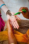 'A Woman Doing Henna Painting On Another Woman's Arm; Sathyamangalam, Tamil Nadu, India'