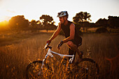 'A Man Riding His Bike Through Tall Grass At Sunset In Parque Natural Los Alcornocales; Tarifa, Cadiz, Andalusia, Spain'
