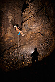 'Male Athlete Ascending A Rope To Exit A Cave; Fernie, British Columbia, Canada'