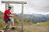 'Male Hiker On Top Of A Mountain Stepping Into An Open Wooden Door And Frame Overlooking A Mountain Valley, Lake And Mountain Range; Oberstdorf, Germany'