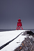 'A Red Lighthouse Under A Stormy Sky Along The Coast In Winter; South Shields, Tyne And Wear, England'