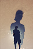 'A Person's Reflection And Shadow On The Wet Sand; Perth, Australia'