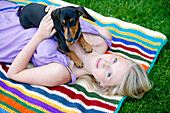 'Woman Relaxing With Her Miniature Dachshund; Victoria, Vancouver Island, British Columbia, Canada'