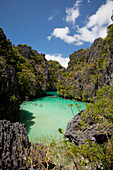 'Tourists Kayak Inside The Scenic Small Lagoon On Miniloc Island, Near El Nido; Bacuit Archipelago, Palawan, Philippines'